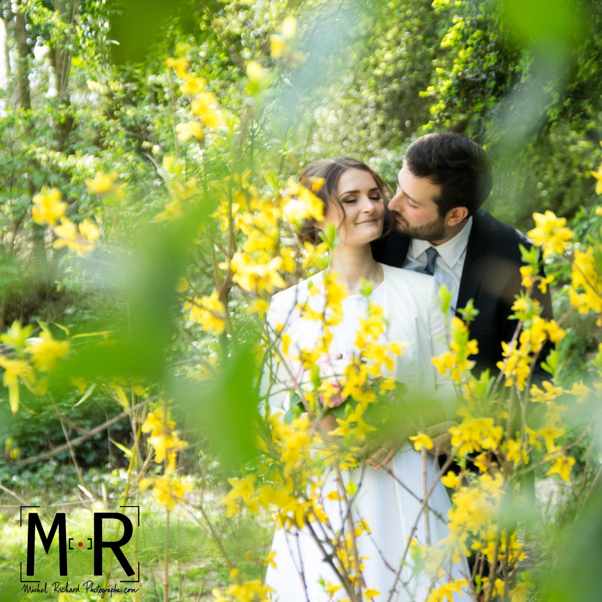 les mariés s'embrassent à travers les feuillages et les fleurs jaunes. Michel Richard Photo