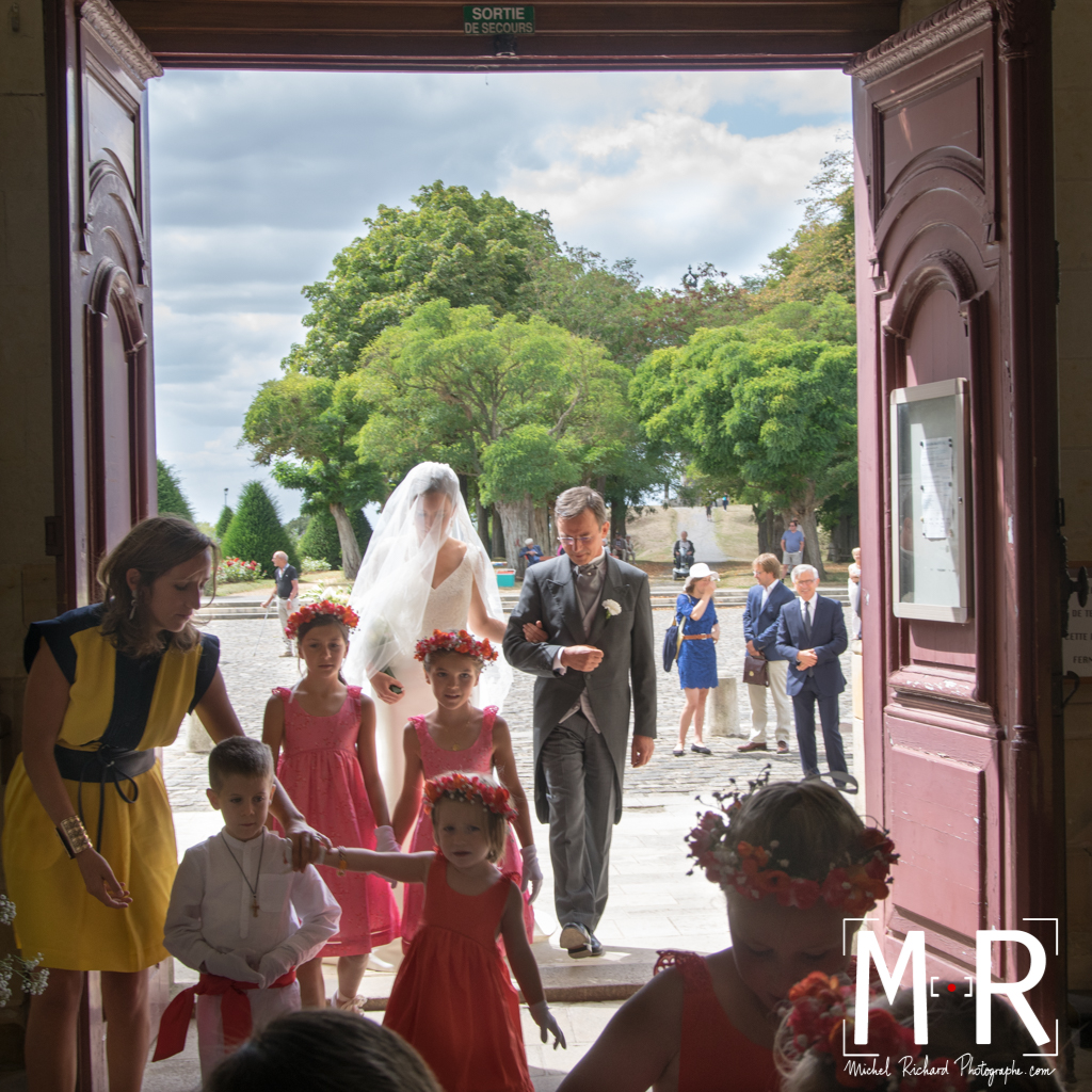 la mariée et son père rentrent dans l'église derrière le cortège des enfants d'honneur. éclairage sur le voile de la mariée, pour la cérémonie religieuse du mariage