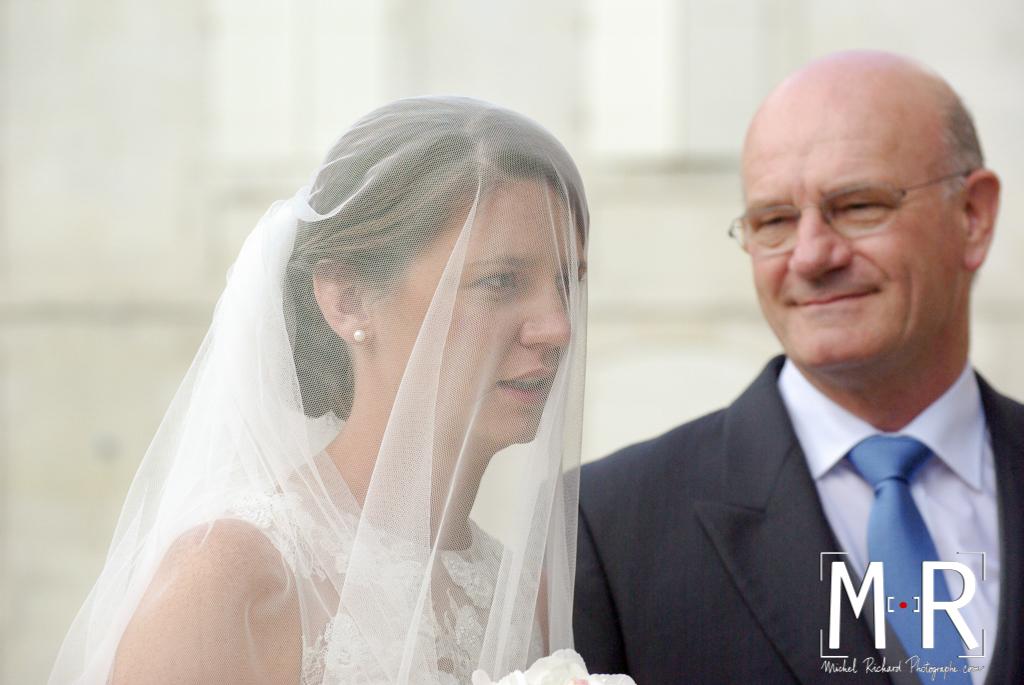 le père de la mariée la regarde sous son voile avant de rentrer pour la cérémonie de mariage à l'église avant la messe.