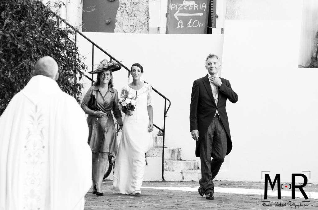 la mariée arrive à l'église avec ses parents pour la cérémonie de son mariage. Le prêtre avance vers la mariée avant la messe.
