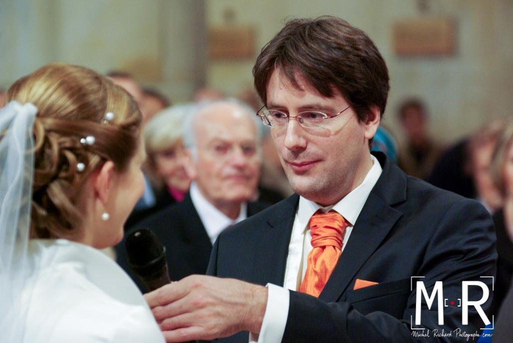 le marié regarde la mariée qui dit oui pendant l'échange des consentements à l'église pour la cérémonie de la messe de mariage
