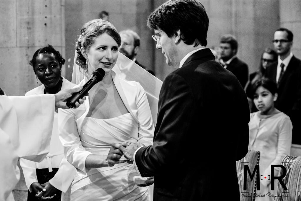 la mariée dit oui et enfile l'alliance au marié à l'église, pendant l'échange des consentements lors de la cérémonie de mariage.