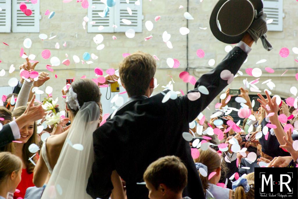 les mariés de dos à la sortie de l'église avec une pluie de pétales. Le marié a un chapeau après la cérémonie, la messe de mariage.
