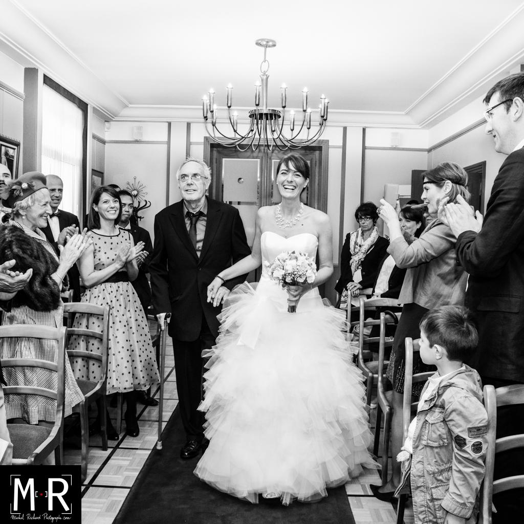 la mariée entre aux bras de son père pour la cérémonie de mariage à la mairie