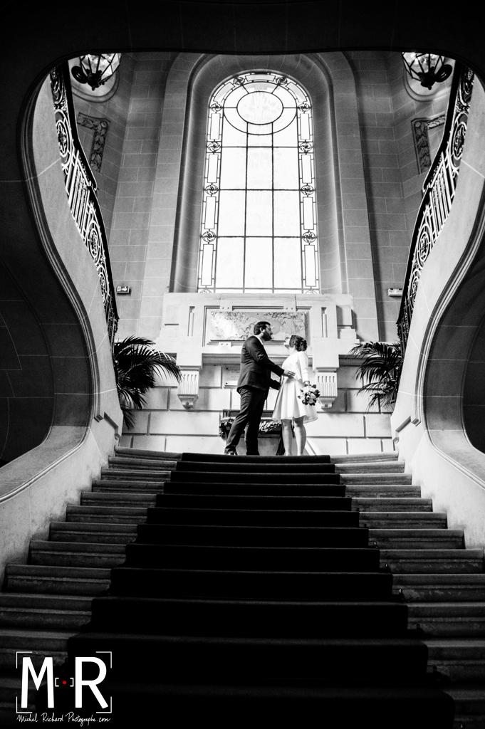 les mariés s'embrassent en haut de l'escalier de la mairie après la cérémonie de mariage