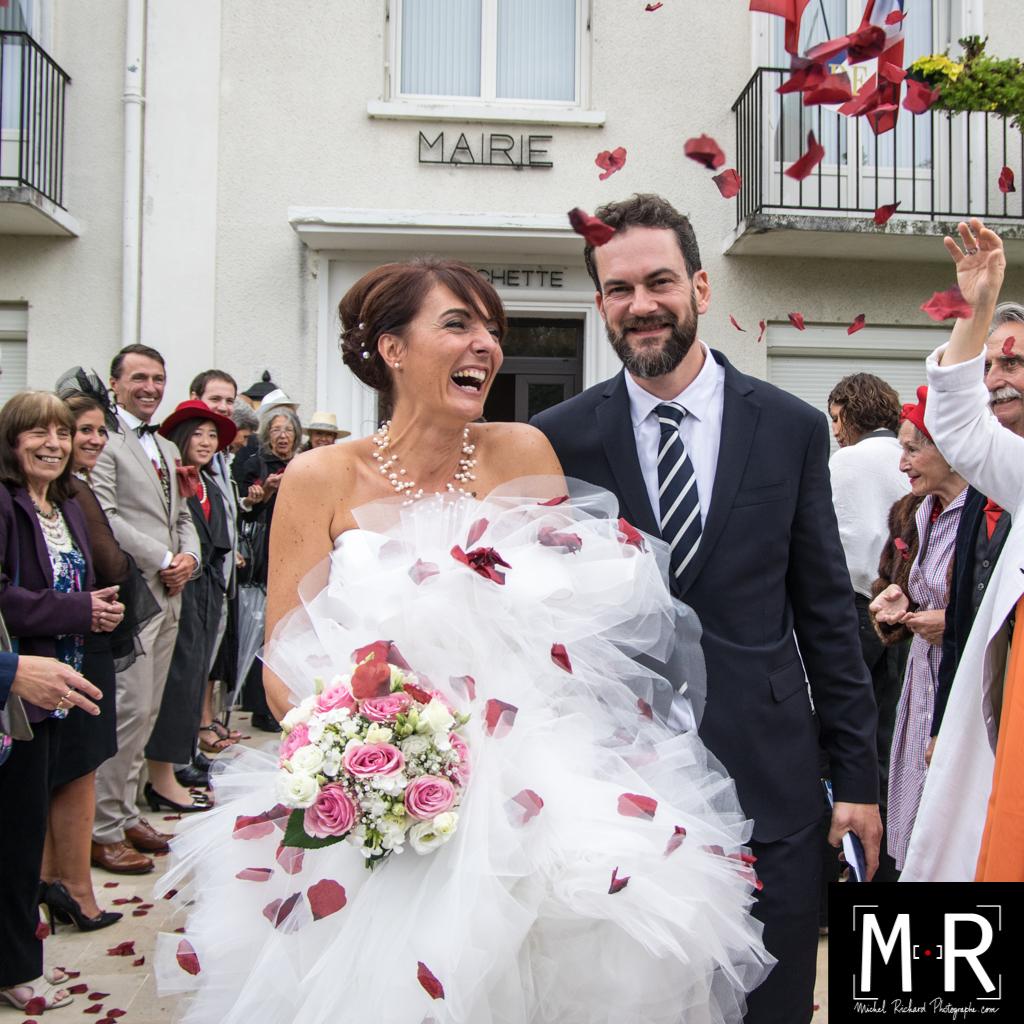 les mariés sortent de la mairie en riant sous les pétales après la cérémonie