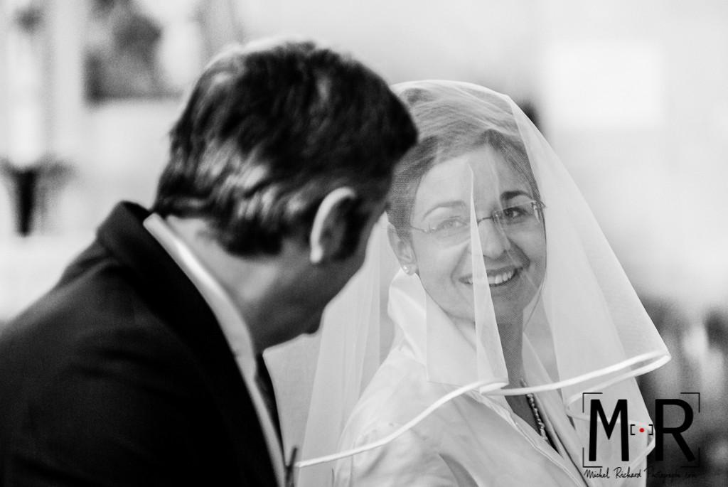 la mariée a un beau sourire pour le marié pendant la cérémonie de mariage à l'église, pour la messe de mariage.
