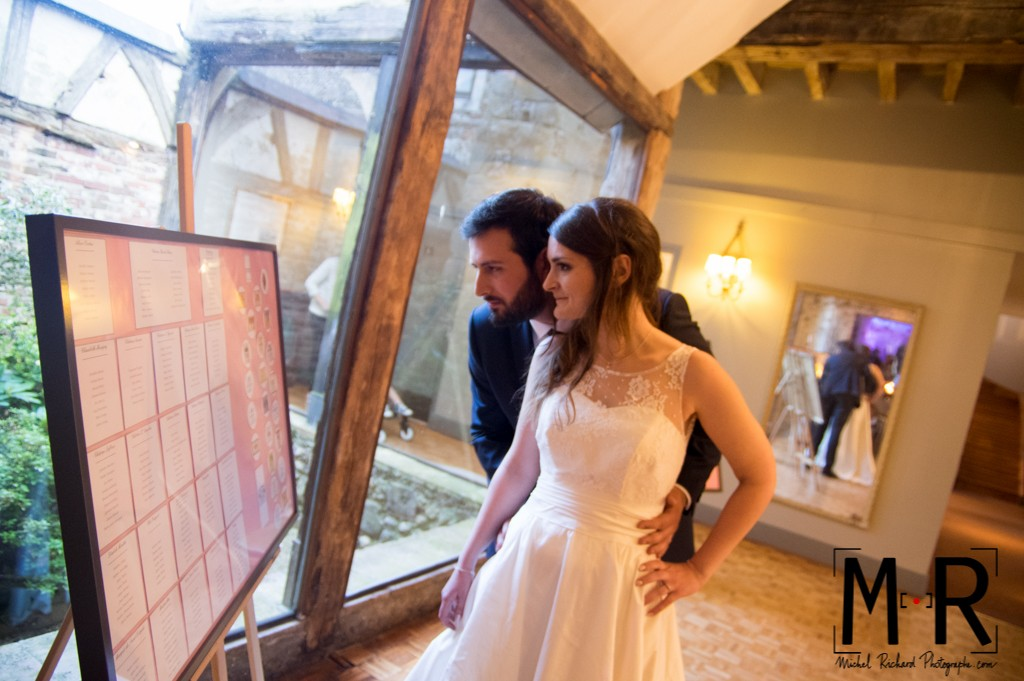 les mariés regardent le plan de table.