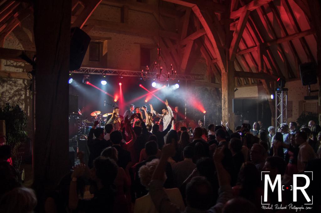 les invités et les mariés dansent dans une grange avec un éclairage de soirée