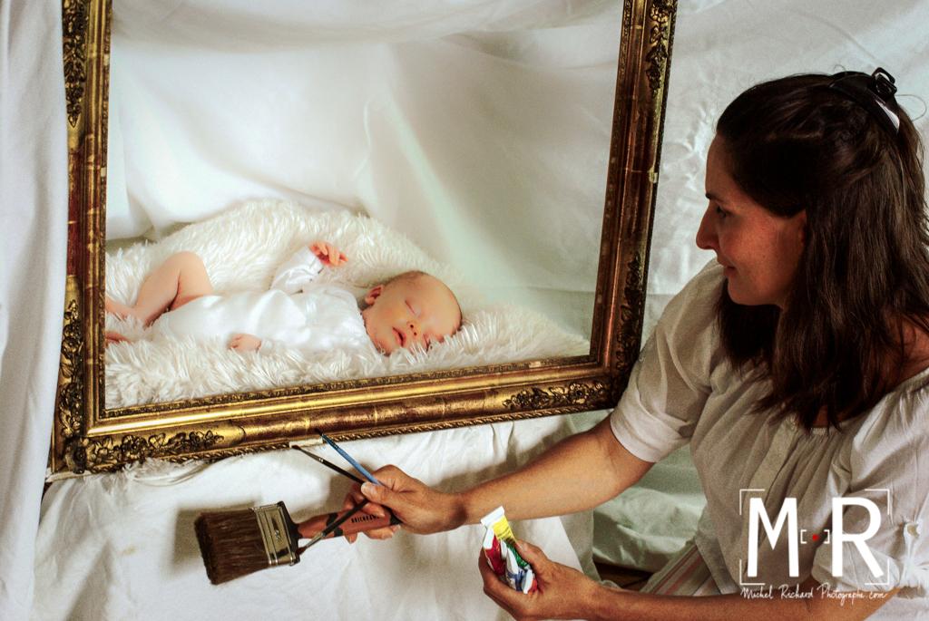 maman regarde bébé dans un cadre tableau. maman tient des tubes de peinture.