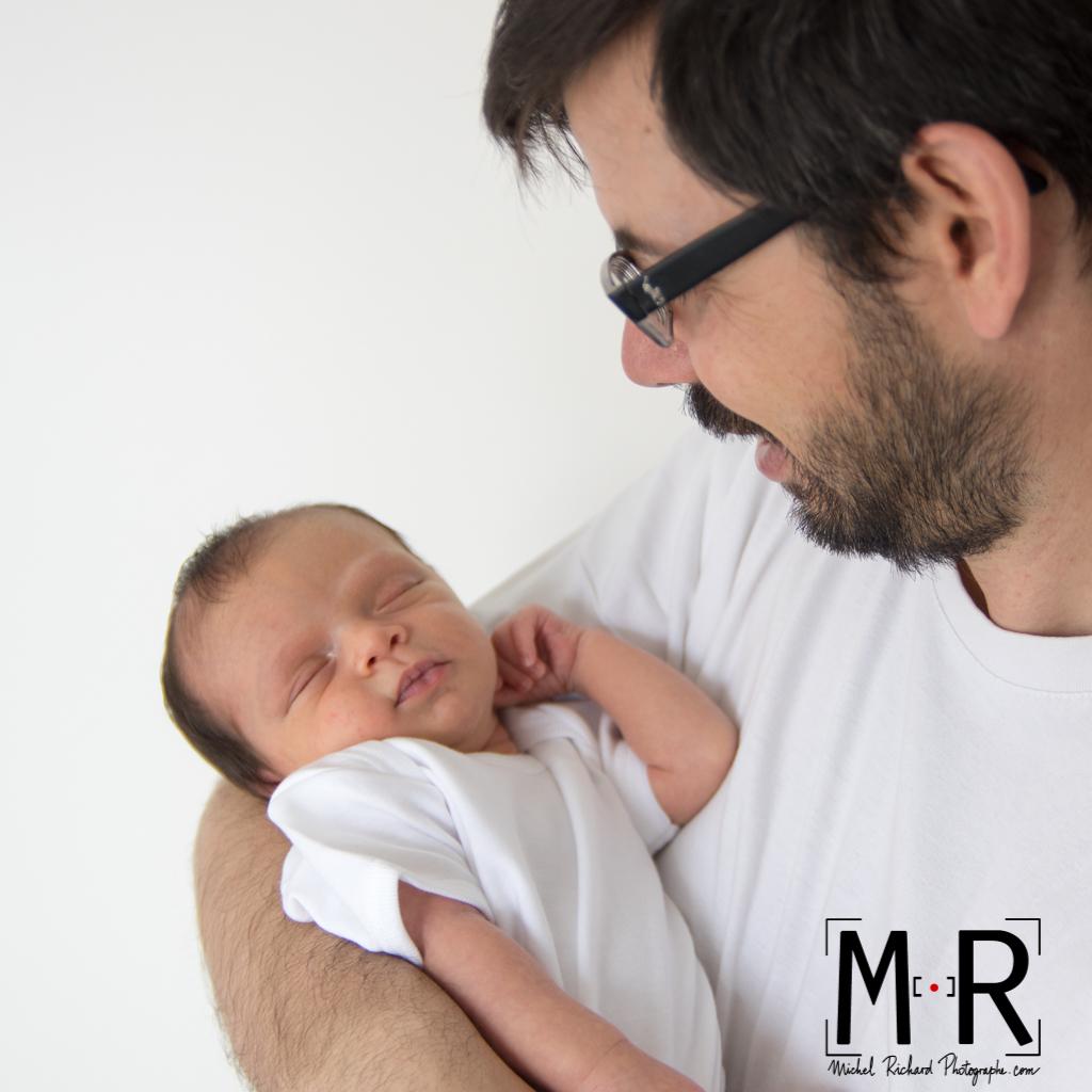 papa sourit et regarde bébé endormi dans ses bras.
