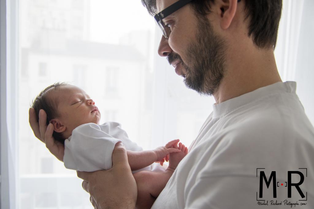 papa contemple bébé endormi devant la fenêtre. le père tient le nouveau-né.