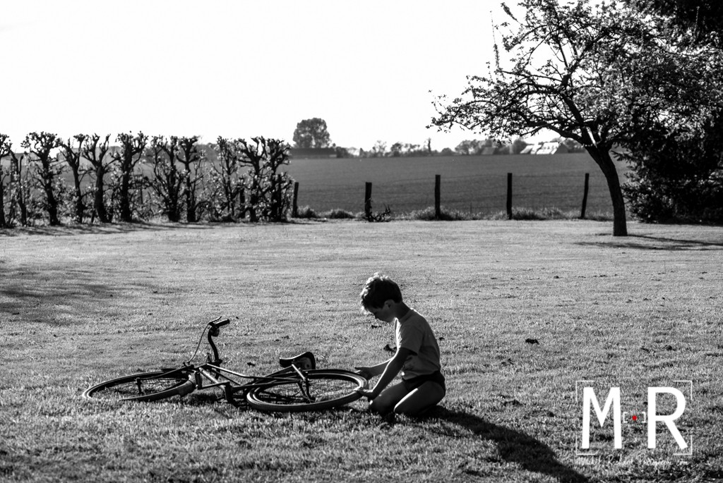 enfant au vélo à la campagne. Le garçon répare son vélo. Noir et blanc