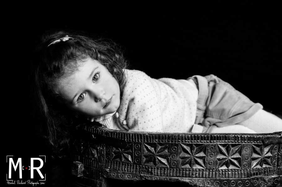 un enfant allongé sur une table ethnique en bois, fonds noir, noir et blanc