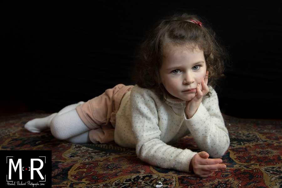 un enfant allongé sur un tapis ancien, fonds noir