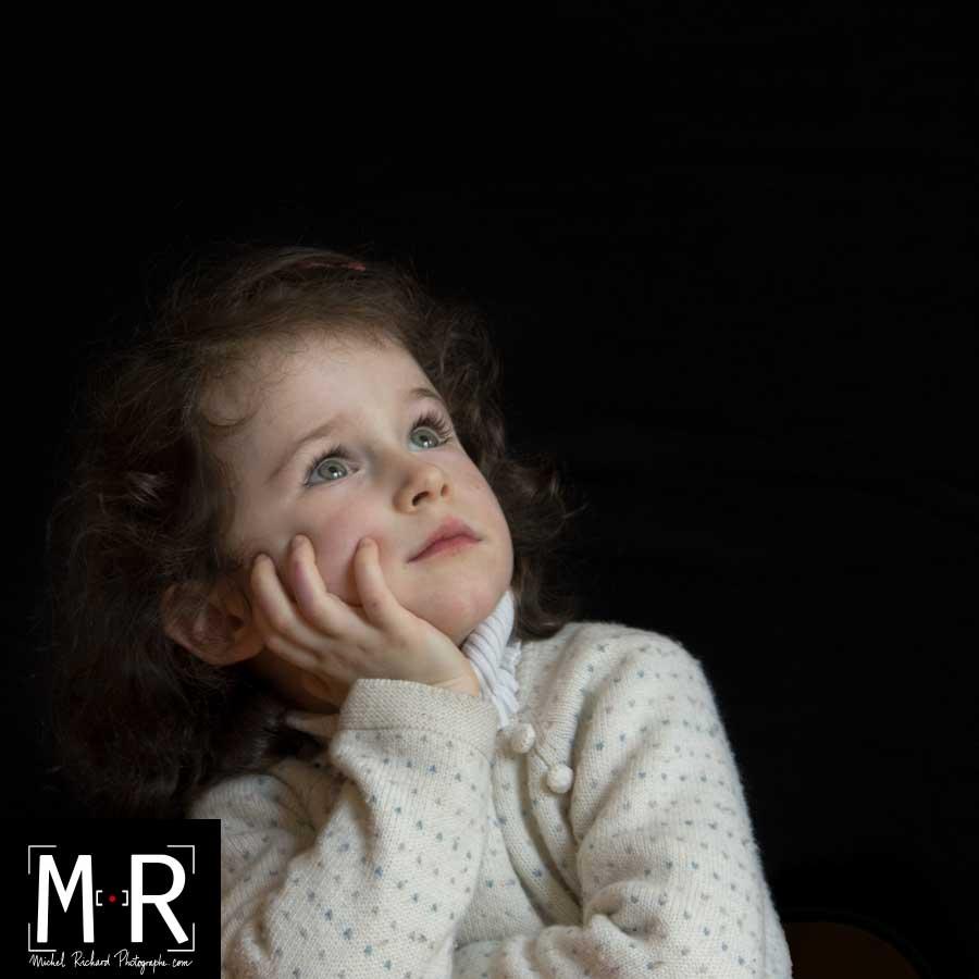 une petite fille rêveuse regarde en l'air. fonds noir, carré
