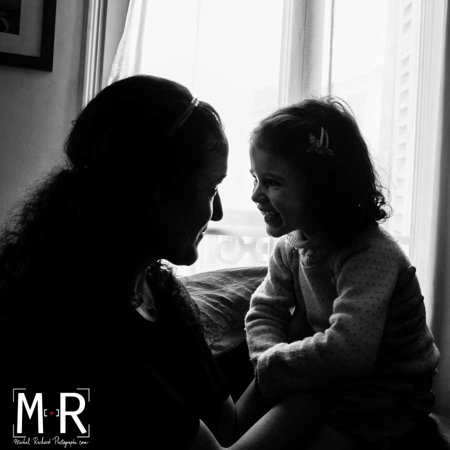 Une fille et sa mère ont un regard tendre en contre-jour devant une fenêtre. Photo noir et blanc