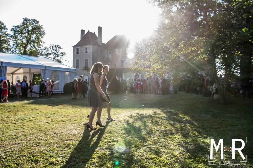 deux filles marchent pendant le cocktail devant le chateau. effet flare du soleil