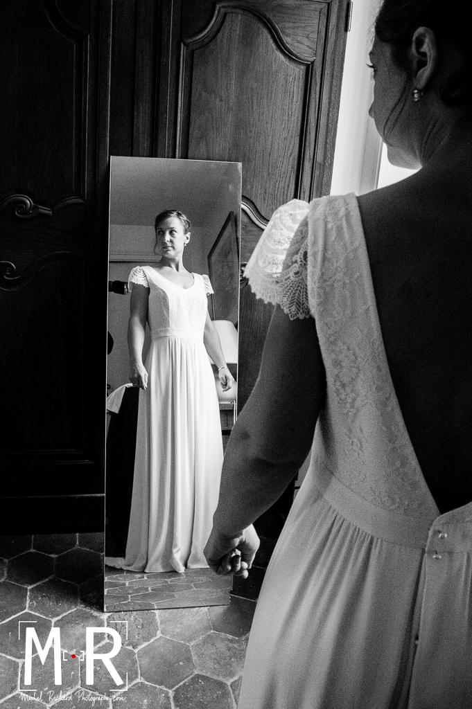 la mariée regarde sa robe dans un miroir