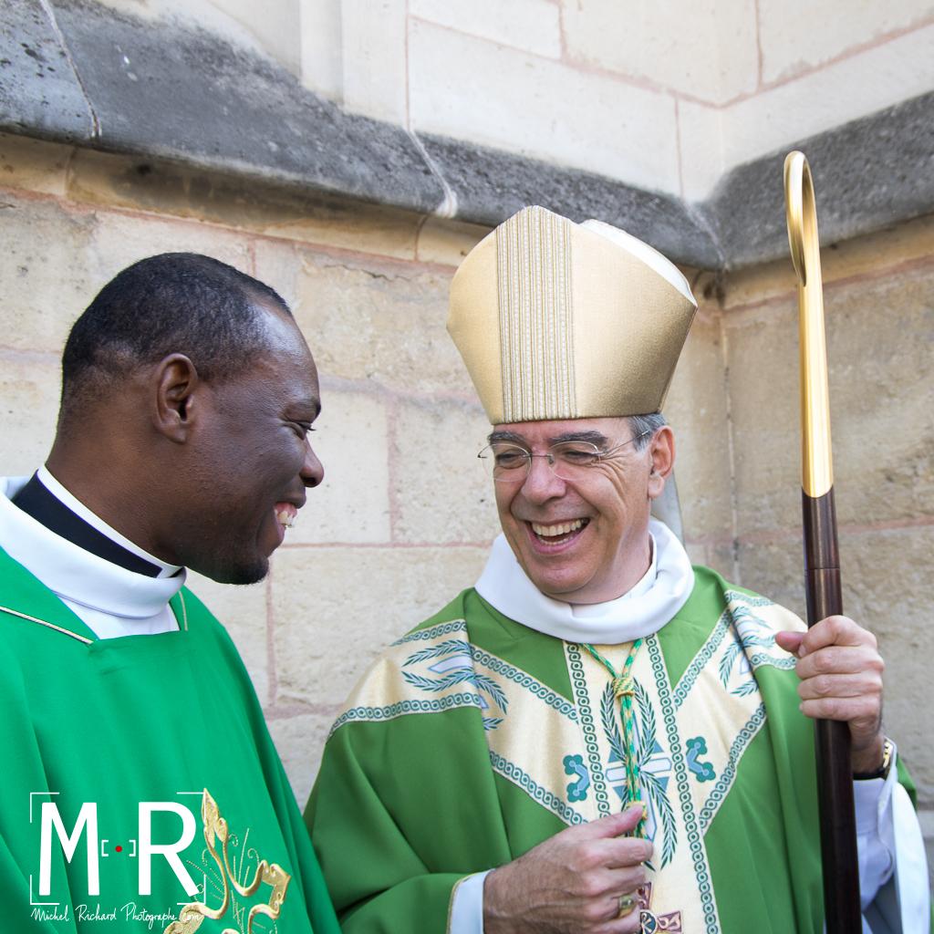 l'évêque rit avec un prêtre