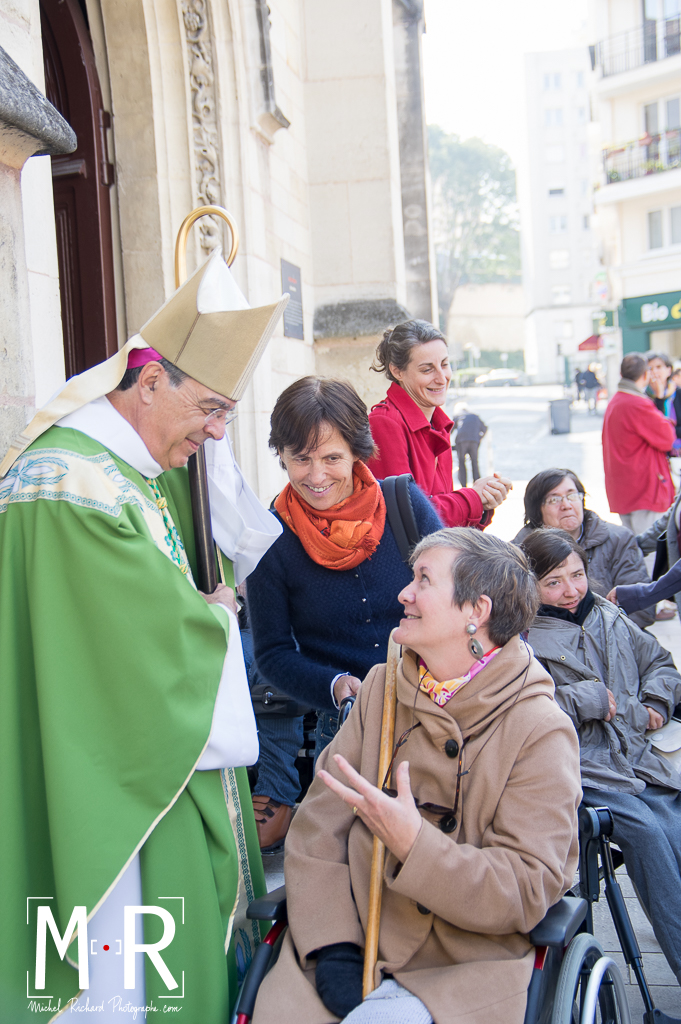 l'évêque écoute joyeusement une personne handicapée en fauteuil roulant