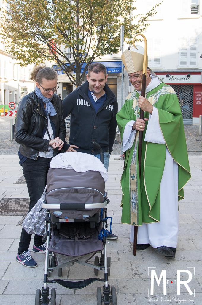 L'évêque et les parents devant le landeau d'un nouveauu-né