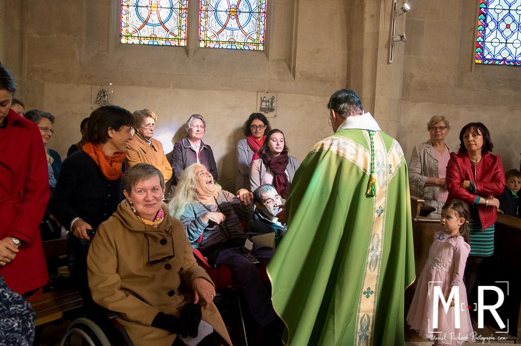 l'évêque donne la paix joyeusement à des handicapés en fauteuil roulant