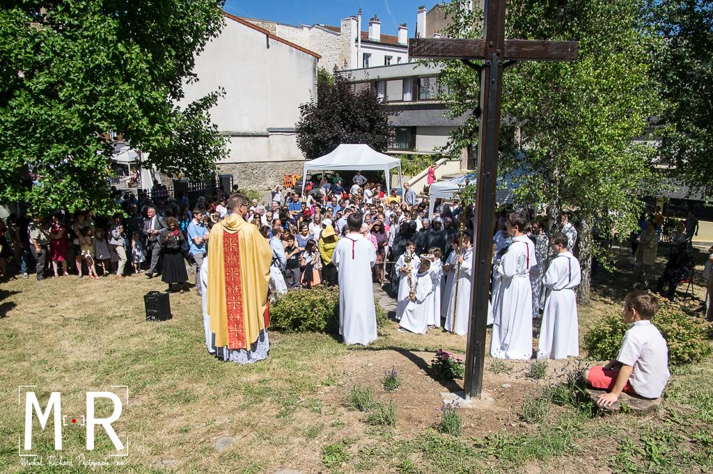 prêtre et enfant de choeur devant une croix dans un jardin