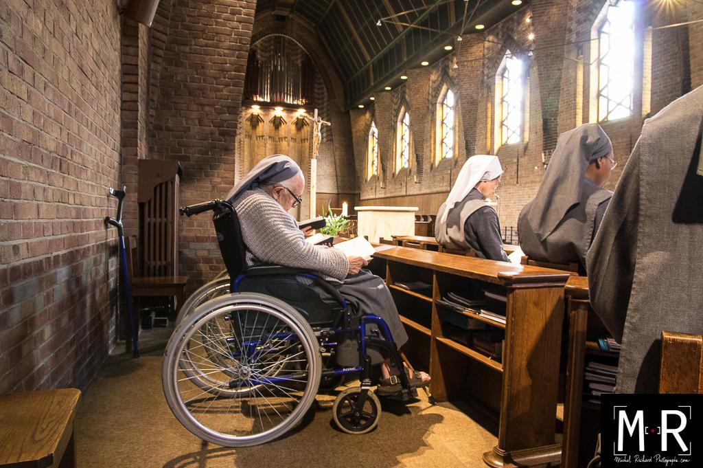 Une religieuse agée prie en fauteuil roulant
