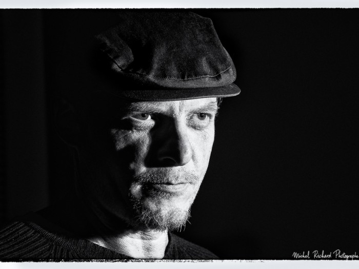 portrait d'homme à casquette au visage buriné clair-obscur en noir et blanc - portrait au flash par le photographe de portrait à Paris Michel Richard