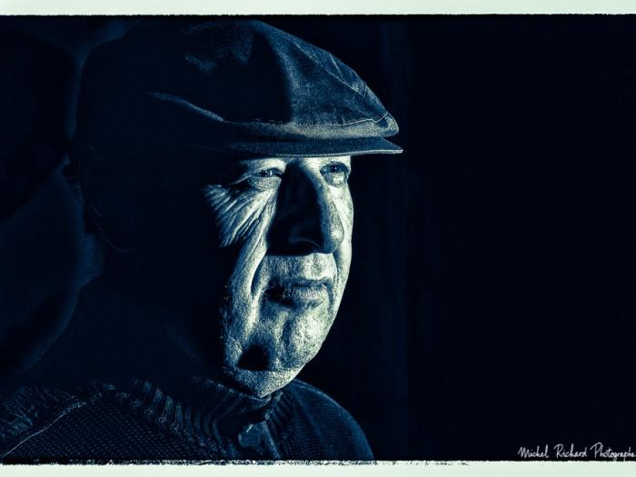 portrait d'homme à casquette au visage buriné en clair obscur et en noir et blanc -couleurs froides - portrait au flash par le photographe de portrait à Paris Michel Richard