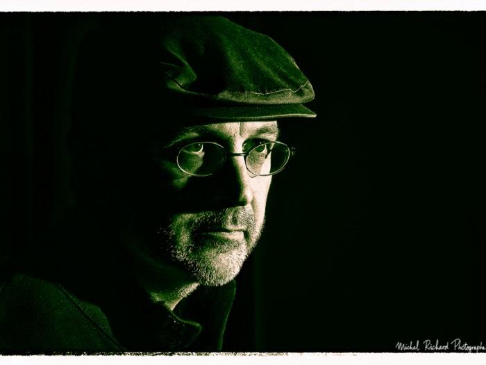 portrait d'homme à casquette au visage buriné en clair obscur et en noir et blanc - couleurs chaudes- portrait au flash par le photographe de portrait à Paris Michel Richard