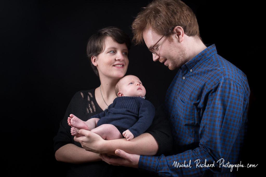 bébé nouveau-né regarde son père. maman regarde papa. séance photo en studio avec photographe professionnel
