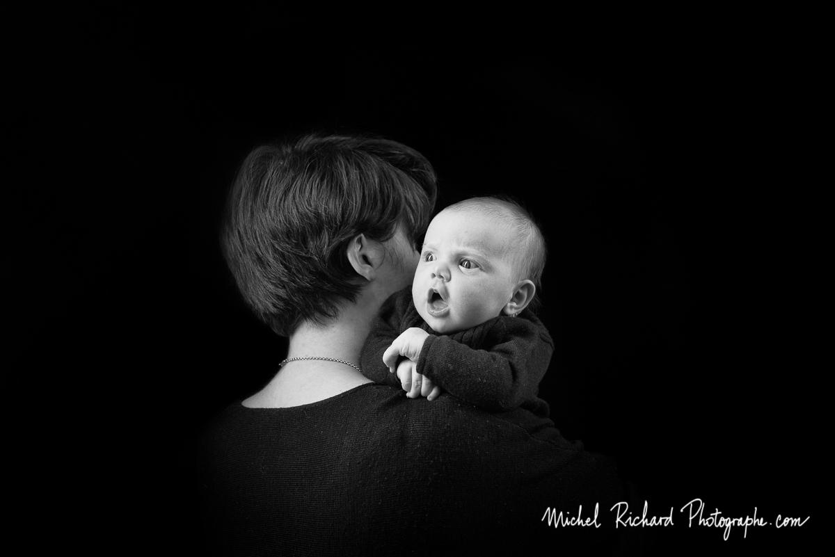 un bébé nouveau-né dans les bras de sa mère. séance studio.