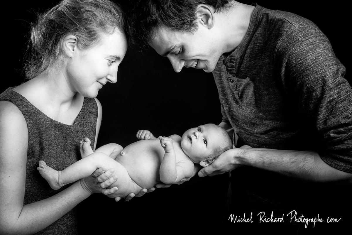 bébé éveillé tenu par ses parents, papa et maman. séance studio bébé.