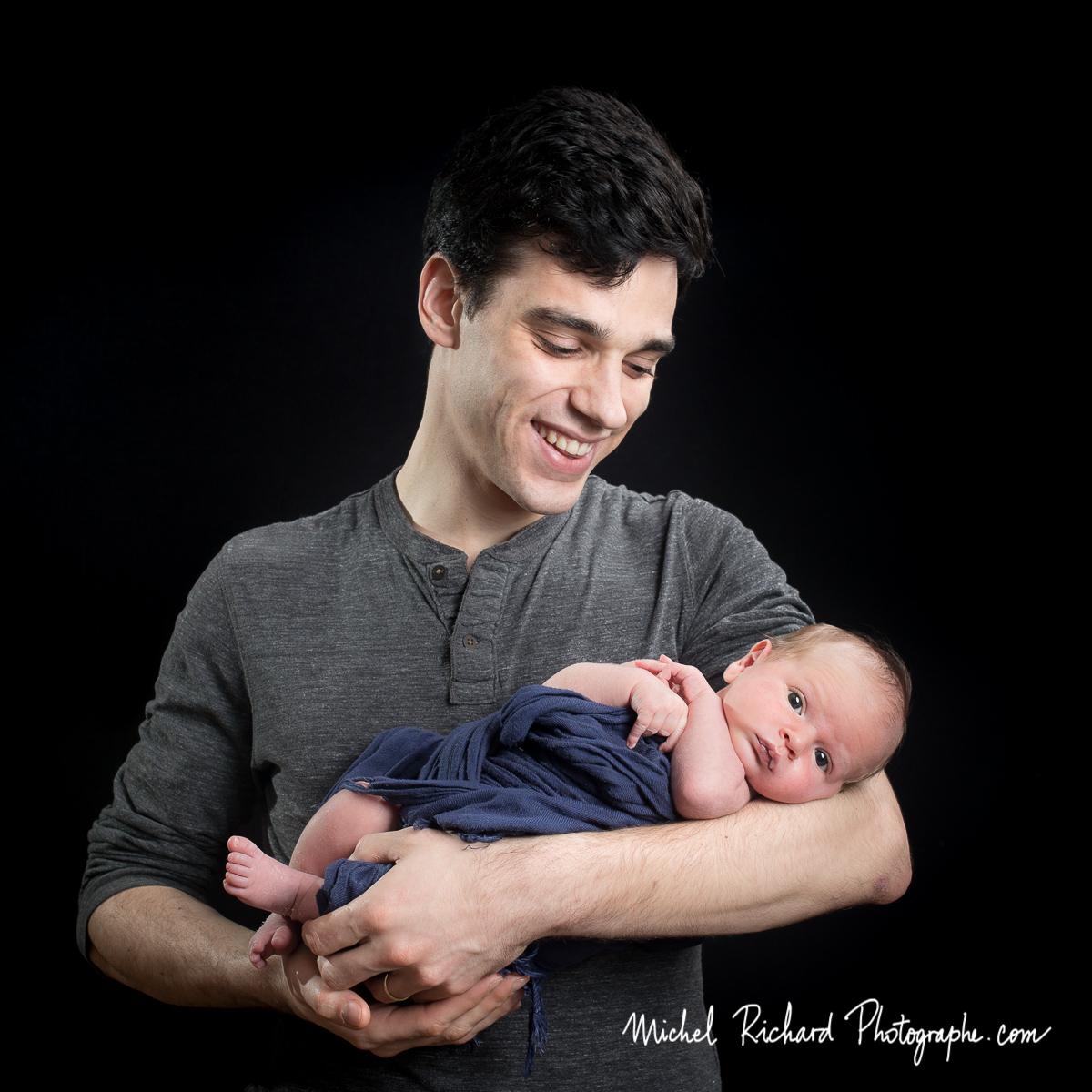 père tient son bébé dans les bras.