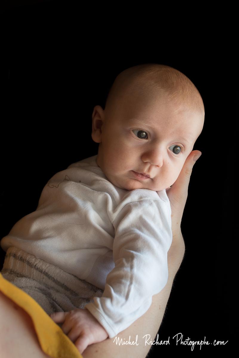 bébé avec un regard calme dans les bras de sa mère