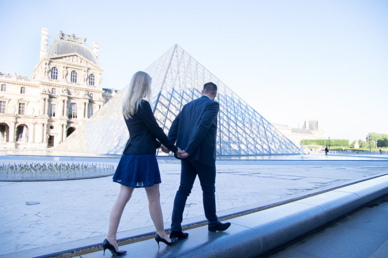 lovers walking in Paris in front of the Louvres pyramid