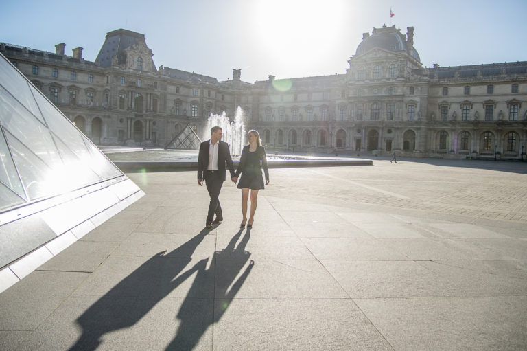 lovely couple in Paris in the Louvres with fountain and shadows figures