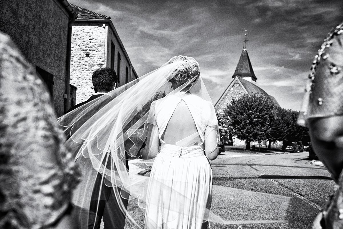 la mariée marche vers l'église, au bras de son père - Paris-Yveline-Oise-Essonne